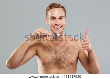 Cheerful young man holding toothbrush and showing thumbs up over grey background - stock photo