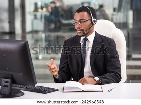 Cheerful young man in headset is looking at laptop. - stock photo