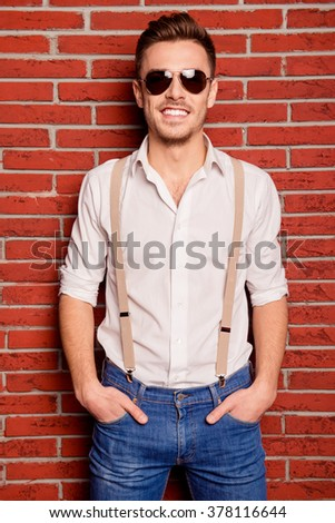 Cheerful young man in spectacles holding hands in pockets of jeans