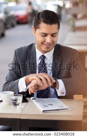Cheerful young man in suit has a business meeting in cafe. He is looking at watch with anticipation. The worker is sitting outdoors and drinking coffee - stock photo