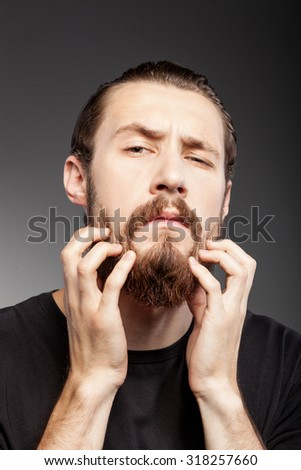 Cheerful young man is scratching his beard. He is looking at the camera with frustration. Isolated on black background - stock photo