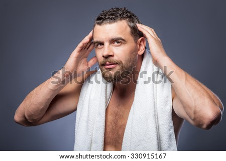 Cheerful young man is standing and touching his hair carefully. He is looking forward with concentration. The man has white towel on neck and beard. Isolated on grey background