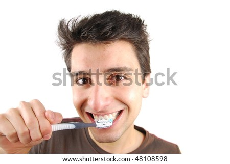 cheerful young man is washing teeth over white background - stock photo