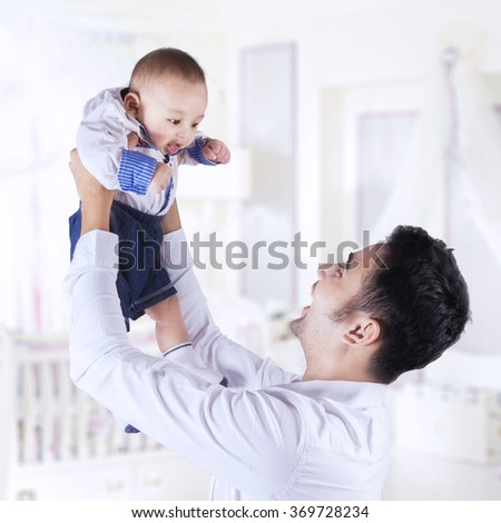 Cheerful young man lift up his baby pride in the bedroom, shot at home - stock photo
