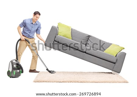 Cheerful young man lifting a sofa and cleaning underneath it with vacuum cleaner isolated on white background - stock photo