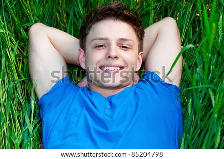 cheerful young man lying on green field - stock photo