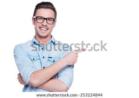 Cheerful young man pointing copy space. Handsome young man in shirt looking at camera and pointing away while standing against white background - stock photo