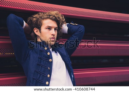Cheerful young man relaxing outdoors on cool wall. Hipster businessman - stock photo