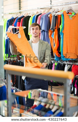Cheerful young man selecting a t-shirt in the store