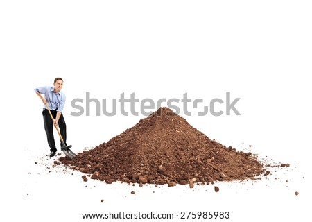 Cheerful young man shoveling a big pile of dirt and looking at the camera isolated on white background