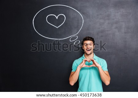 Cheerful young man showing heart by hands standing over blackboard background - stock photo