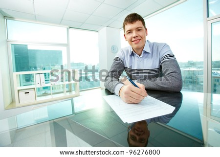 Cheerful young man signing business papers - stock photo