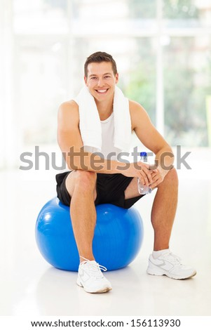 cheerful young man sitting on gym ball, holding water bottle - stock photo