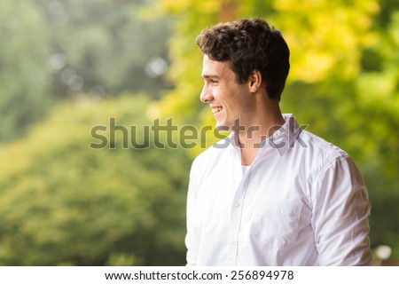 cheerful young man standing outdoors - stock photo