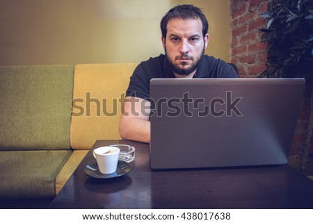 Cheerful young man using laptop in coffee shop. - stock photo