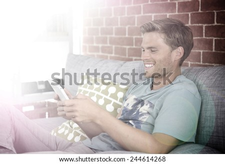 Cheerful young man using tablet in sofa - stock photo
