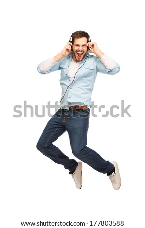 cheerful young man very happy and jumping with headset and listening music on white background - stock photo