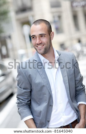 Cheerful young man walking in town