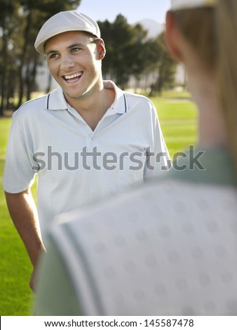 Cheerful young man wearing golf cap with competitor in foreground - stock photo