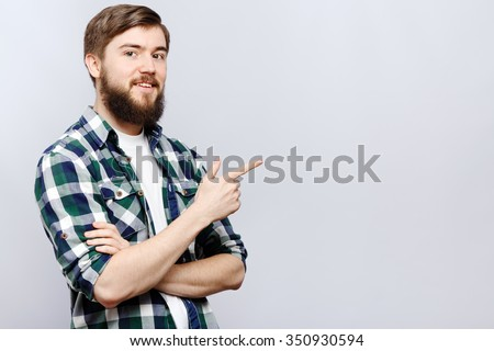 Cheerful young man, wearing on white t-shirt and blue checked shirt, is showing something by his hand, on white background, in studio, waist up - stock photo