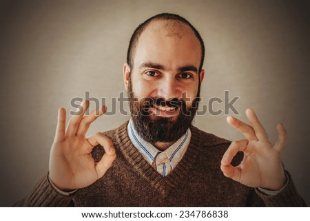 Cheerful young man with a beard in brown sweater gesturing OK sign - stock photo