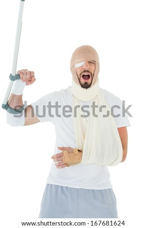 Cheerful young man with broken hand and crutch cheering over  white background - stock photo