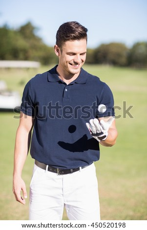 Cheerful young man with golf ball while standing on field