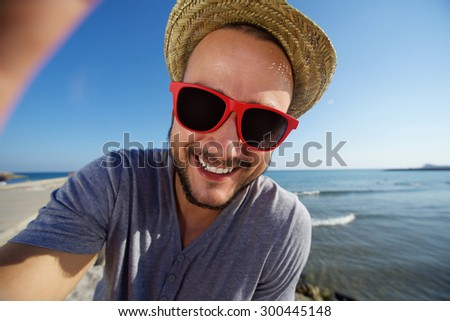 Cheerful young man with hat at the beach taking selfie - stock photo
