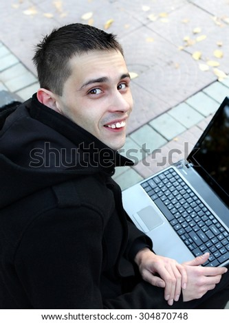 Cheerful Young Man with Laptop on the Bench - stock photo