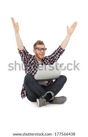 Cheerful young man with laptop raising hands over white background - stock photo