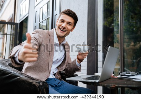 Cheerful young man with laptop showing thumbs up and drinking coffee in outdoor cafe - stock photo