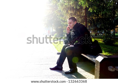 Cheerful Young Man with Mobile Phone at the Autumn Park - stock photo