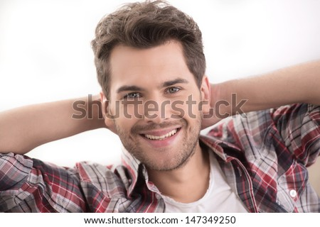 Cheerful young men! Portrait of cheerful young men smiling at camera while sitting on couch - stock photo