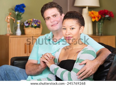 Cheerful young mixed Black and White couple holding hands - stock photo