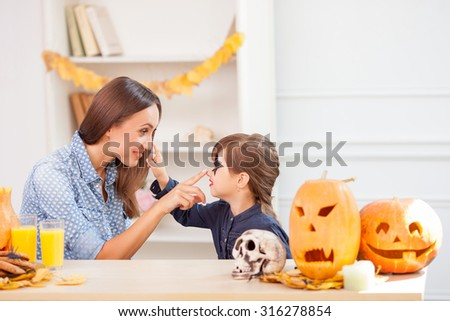 Cheerful young mother and girl are celebrating Halloween. They are sitting at the table and smiling. They are touching each other noses with joy. There are food and pumpkins on the table - stock photo