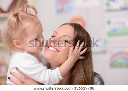 Cheerful young mother is embracing her daughter with love. They are smiling - stock photo
