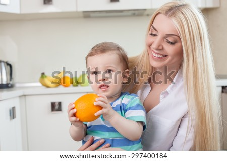 Cheerful young mother is sitting and holding her small son. The boy is holding an orange in his hands with appetite. The woman is looking at her child with love and smiling. Copy space in left side - stock photo