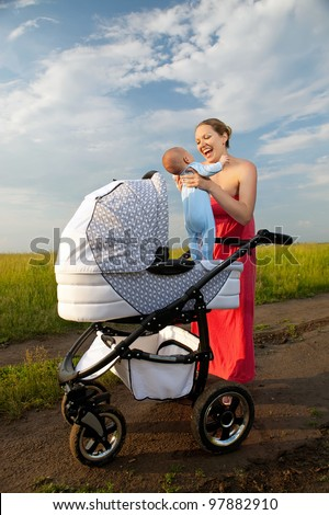 Cheerful young mother taking her baby boy out of the pram - stock photo