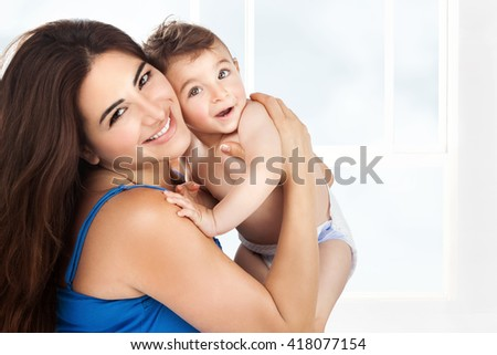 Cheerful young mother with her cute little son playing at home, with pleasure spending time together, happy family life - stock photo