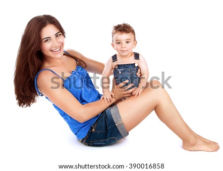 Cheerful young mother with her cute little son sitting on the floor and playing in the studio, isolated on white background, happy family together - stock photo