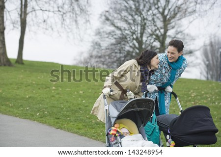 Cheerful young mothers pushing strollers in park - stock photo