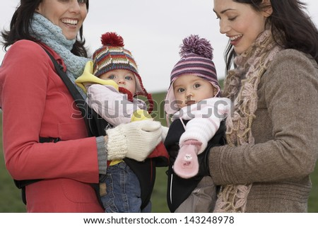 Cheerful young mothers with babies in slings at park - stock photo
