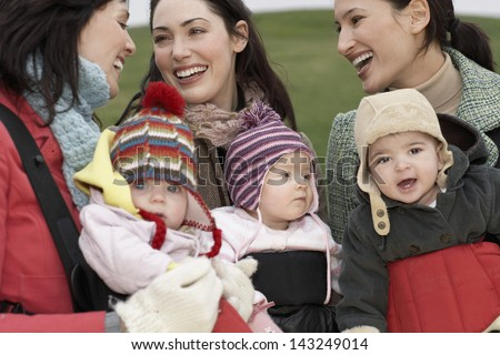 Cheerful young mothers with babies in slings chatting outdoors - stock photo