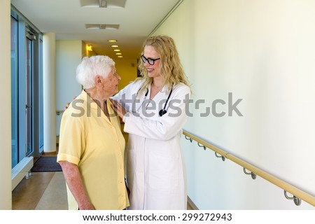 Cheerful Young Nurse Assisting a Senior Woman with Special Needs Walking at the Corridor Inside the Hospital.