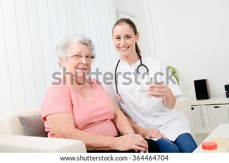 cheerful young nurse giving drug prescription to an elderly woman at home - stock photo