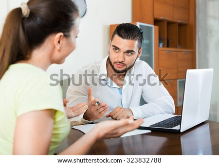 Cheerful young pair with financial papers and notebook indoors