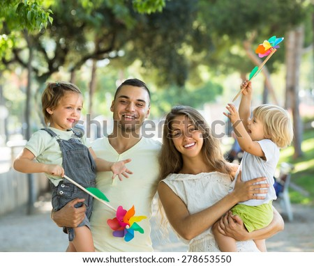 Cheerful young parents holding kids with toy windmills at summer day
