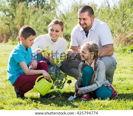 Cheerful young parents with two children planting a tree and watering it together - stock photo