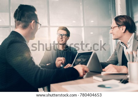 Cheerful young partners telling with each other while locating at desk in office. Career concept