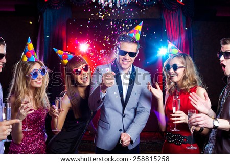 Cheerful young people showered with confetti on a club party. - stock photo